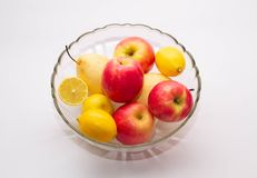 Apples, pears, lemons in a transparent glass plate on a light background royalty free stock photo