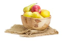 Apples and pears in rustic wooden fruit bowl on sackcloth. Red and yellow apples and European pears Bosc in vintage wooden fruit bowl on a sackcloth on a white Stock Photography