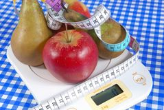 Apples and pears on scale Stock Images