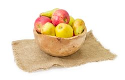 Apples and pears in vintage wooden fruit bowl on sackcloth. European pears Bosc, red and yellow apples in rustic wooden fruit bowl on a sackcloth on a white Stock Image