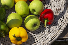 Apples and peppers in a wicker basket Stock Images