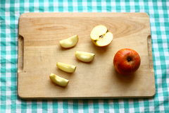 Apples. Pieces of an organic red apple on wood and green tablecloth Royalty Free Stock Photos