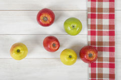 Apples placed on red checkered kitchen tablecloth. Top view. Colored whole apples placed on red checkered kitchen tablecloth. Top view Royalty Free Stock Images