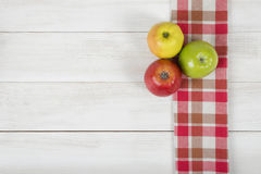 Apples placed on red checkered kitchen tablecloth. Top view. Colored whole apples placed on red checkered kitchen tablecloth. Top view Stock Image