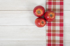 Apples placed on red checkered kitchen tablecloth. Top view. Colored whole apples placed on red checkered kitchen tablecloth. Top view Royalty Free Stock Photos