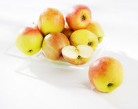 Apples on a plate. Apples on a glass plate on a white background stock photography