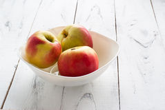 Apples in the plate. Red and yellow apples in the plate on white wooden table Stock Images
