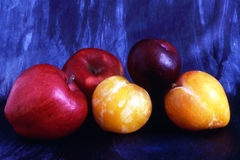 Apples and plums isolated on painted background Royalty Free Stock Photo