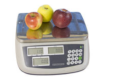 Apples on produce scale. Three apples on a digital produce scale isolated on white Royalty Free Stock Photo