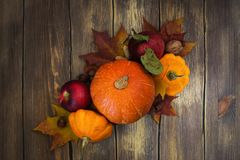 Apples, pumpkins and autumn leaves over wooden background Stock Images
