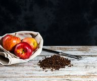 Apples recipe with cloves and knife. Recipe with cloves and apple on an old wooden white table. Non uniform dark background with free space for text Stock Photos