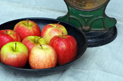 Apples and scale. Seven red apples (pink lady) in the tray of an old cast iron scale; an apple a day concept Stock Photo
