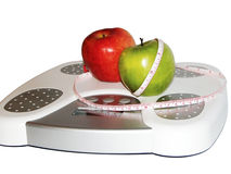 Apples on scale. Two apples on a scale with measuring tape Royalty Free Stock Image