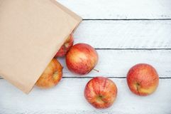 Apples are scattered from the kraft package on a white wooden background. royalty free stock photos