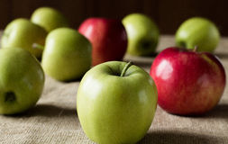 Apples scattered on the table. Red and green apples scattered on the table, covered sackcloth Stock Images