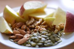 Apples and Seeds. Close up view of sliced apples and pumpkin seeds, almonds, and walnuts Royalty Free Stock Photos