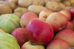 Apples on a shelf. Closeup photo of apples on a shelf together with cabbage and potatoes Royalty Free Stock Images