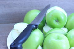 Apples are sliced with a knife on a plate placed on a gray Stock Photography