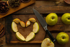 Apples sliced with knife for cooking pie. Royalty Free Stock Photography