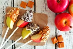Apples slices dipped with chocolate, caramel, scene on white wood Royalty Free Stock Image