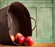 Apples spilling out of basket on grunge background Royalty Free Stock Photos