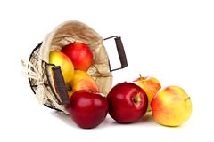 Apples spilling from a rustic basket isolated on white Stock Images