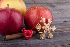 Apples, stars from straw  and cinnamon. With red bow on wooden background Royalty Free Stock Photo