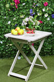 Apples, strawberries and flowers on white table. Next to green hedge Stock Photos