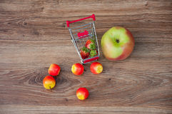 Apples, strawberries and small shopping cart on table Stock Photos