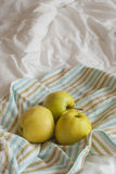 Apples on a striped towel. Three yellow apples on a striped towel, vertical, rustic style Royalty Free Stock Photo