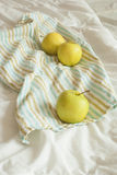 Apples on a striped towel. Three yellow apples on a striped towel, vertical, rustic style Stock Photo