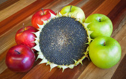 Apples and sunflower on a wooden table Stock Images