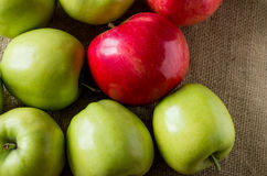 Apples are on the table, covered sackcloth. Red and green apples scattered on the table, covered sackcloth Royalty Free Stock Images