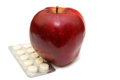 Apples or tablets?. Choice for the person: to eat apples or to swallow of medicines Royalty Free Stock Images