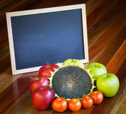 Apples, tomatoes, sunflower and blackboard composition Royalty Free Stock Image