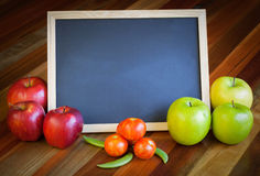 Apples, tomatoes, sunflower and blackboard composition Royalty Free Stock Images