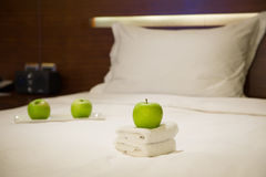 Apples and towels on bed Stock Photo
