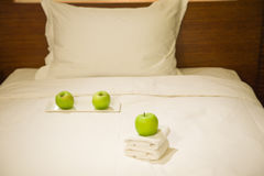 Apples and towels on bed Stock Images