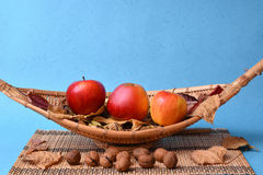 Apples and walnuts on wooden bamboo fruits plate Stock Image