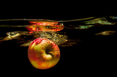 Apples in water with reflrction and splash Royalty Free Stock Images