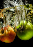 Apples in water with reflrction and splash Stock Images