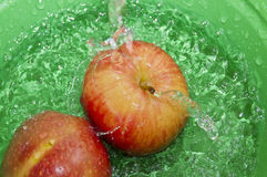 Apples on water splash. In green background Royalty Free Stock Photo