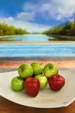 Apples in white plate. Red and green apples on a white ceramic plate, outdoor in a park Royalty Free Stock Photo