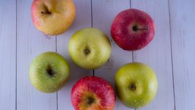 Apples on a white wooden table. Harvest of green and red apples. royalty free stock images