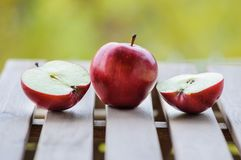 Apples whole and cut in halves on wooden surface. Close up image of one whole red apple and two halves on wooden surface outdoors Stock Photo