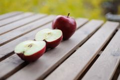 Apples whole and cut in halves on wooden surface. Close up image of one whole red apple and two halves on wooden surface outdoors Stock Images