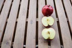 Apples whole and cut in halves on wooden surface. Close up image of one whole red apple and two halves on wooden surface outdoors Royalty Free Stock Photo