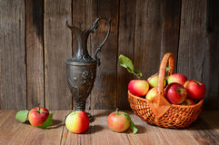 Apples in a wicker basket with a antique metal jug Royalty Free Stock Photography