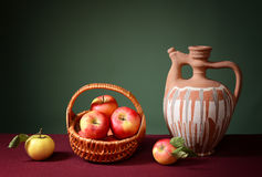 Apples in a wicker basket with a ceramic jug Stock Images