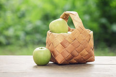 Apples in wicker basket on table. Rustic vintage style photo Stock Image